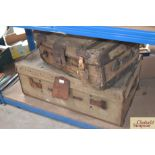 A canvas and leather wheeled trunk and a strapped