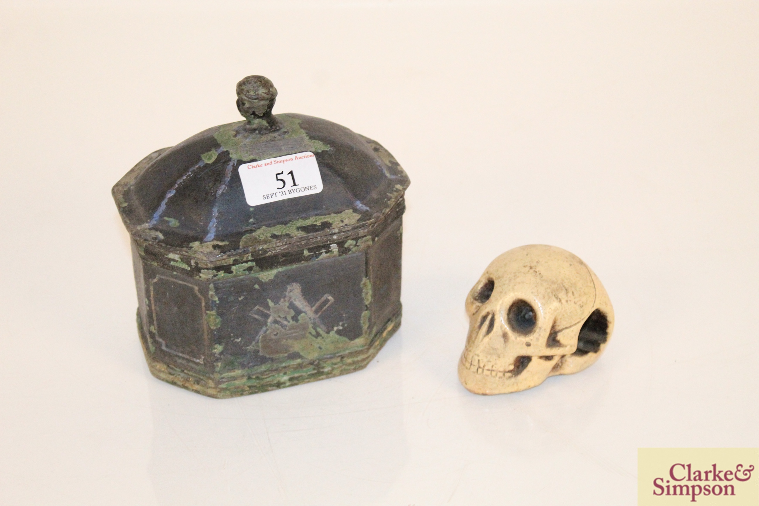 A lead casket containing a faux ivory skull