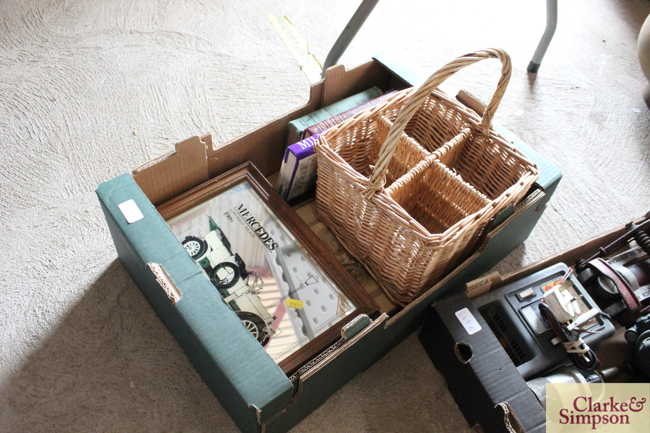 A box containing a wicker bottle carrier, three ca