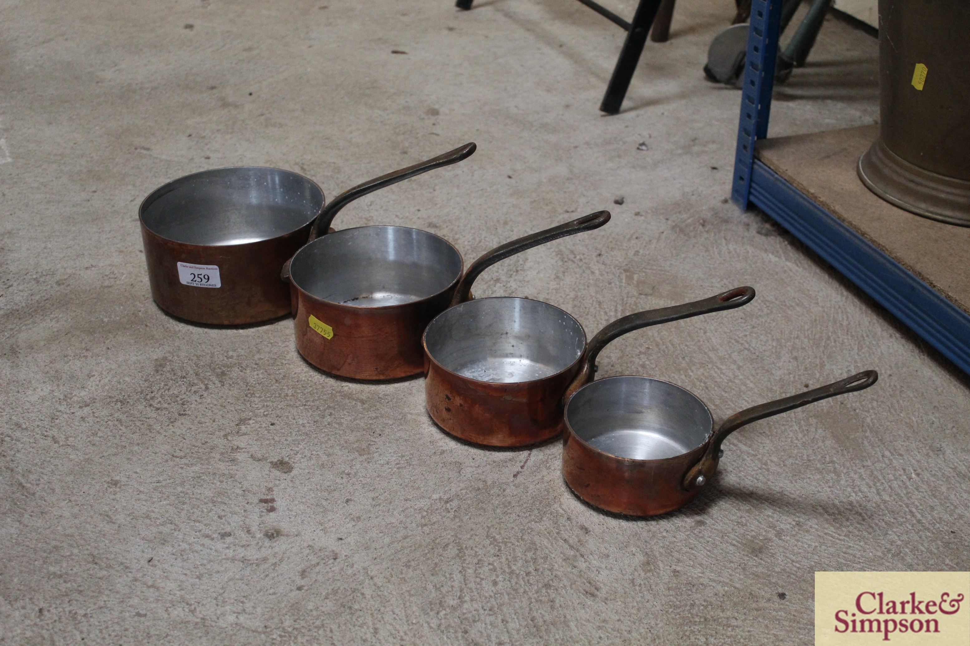 A set of four graduated copper saucepans with iron
