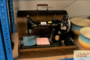 A Singer hand sewing machine in fitted case