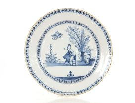 An 18th Century English Delftware blue and white charger,painted with an Oriental figure smoking