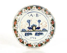 A rare 18th Century Bristol Delftware polychrome plate,naively painted with initials A.B. dated
