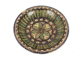 A North African glazed pottery shallow dish,having multi coloured stylised decoration, 35cm dia.