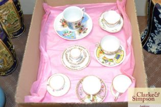 A box containing seven miniature cups and saucers