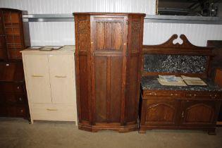 An oak linen fold decorated wardrobe