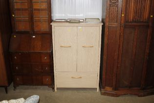 A beech effect cupboard fitted with a single drawe