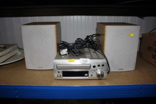 A Denon CD player with a pair of speakers