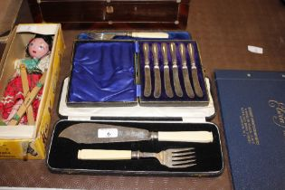 A pair of cased plated fish servers, a plated cake