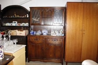 An oak and leaded glazed dresser with linen fold d