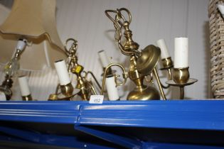 A pair of brass three branch ceiling lights