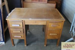An oak desk fitted with six drawers