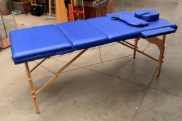 A Healthline Massage Products folding massage bench upholstered in blue PVC complete with carry bag,