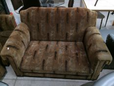 A 1920s brown patterned three piece suite comprising two seater settee and two armchairs