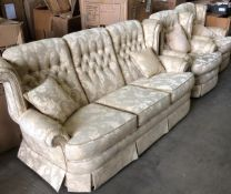A beige and gold leaf patterned three piece suite comprising three seater settee and two armchairs