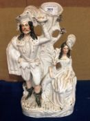 A Staffordshire style man and woman with deer figure group