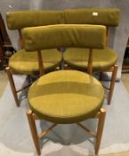 Three G Plan teak framed dining chairs with circular green upholstered pad seats and back rail