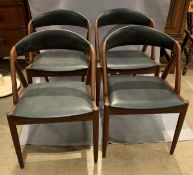 A set of four mid 20th century teak framed dining chairs with black rexine upholstered seats and
