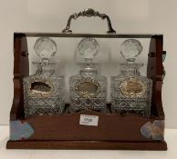 A wood framed Tantalus complete with three crystal glass decanters with silver coloured labels