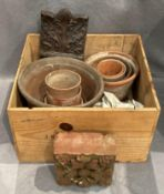 A small wood crate containing a small quantity of assorted sized terracotta plant pots,
