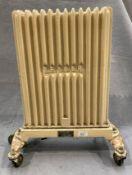 A Dry Denair cast iron mobile radiator 60 x 48cm wide - one cast castor broke off and electric
