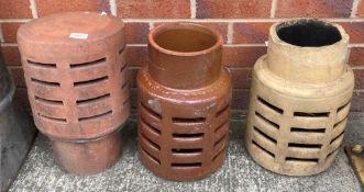 Three various terracotta and salt glazed chimney top pots,