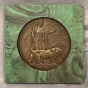 A resin copy of a First World War death plaque to Ernest Edward Smith set in a green marble finish