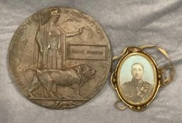 A bronze First World War death plaque to Frank Dobson together with a brass oval pendant with a