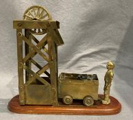 A brass mining model featuring a miner,