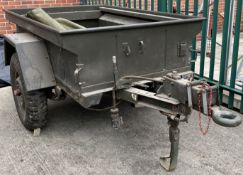 A military green metal single axle trailer, 130cm x 190cm x 147cm deep, complete with cover,