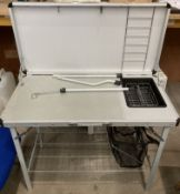 A Hi Gear metal camping table with lift top to convert to a wash/prep station,