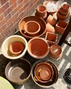 A large quantity of assorted terracotta and other plant pots, plant pot stands,