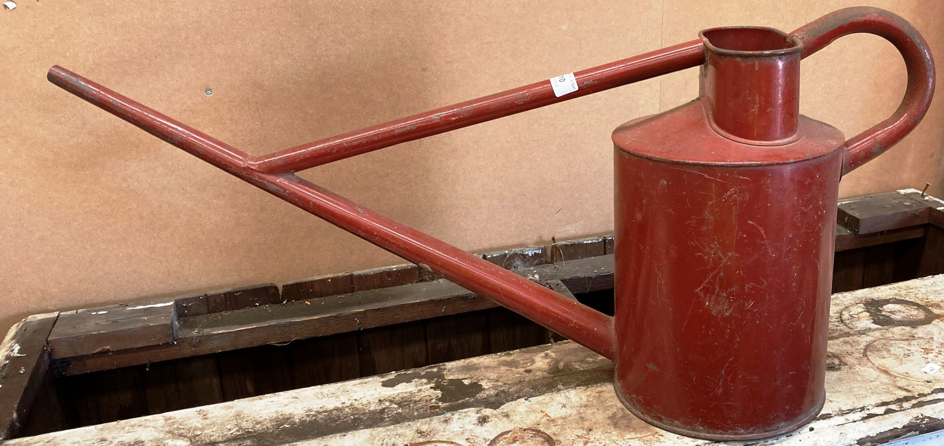 A large red metal watering can