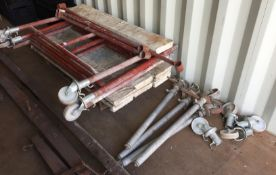 Small red metal scaffold tower comprising four uprights 130 x 100cm high complete with 8 wheels,