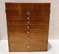 A wooden portable dentist case with lift top and six graduated drawers complete with a quantity of
