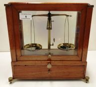 A set of small brass balance scales in a glazed wood framed case with under drawer - case size 28cm