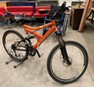 A Carrera Hellcat Shimano Diore 18 speed front and rear suspension mountain bike in orange with