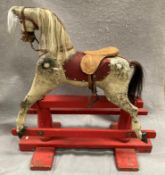 An old dapple grey composition rocking horse on red painted wooden frame, length approximately 80cm,