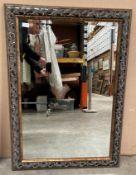 An ornate walnut and black finish framed wall mirror 104 x 75cm