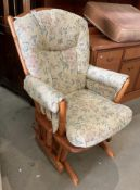A Dutalier wood framed rocking armchair model 11490 with light brown floral patterned upholstery