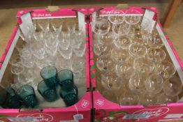 Two trays of drinking glasses including champagne saucers and blue glass whiskies