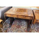 A George IV rosewood sofa table with carved shaped end supports on bold carved paw feet and inset
