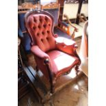 A mid Victorian carved mahogany button back upholstered armchair