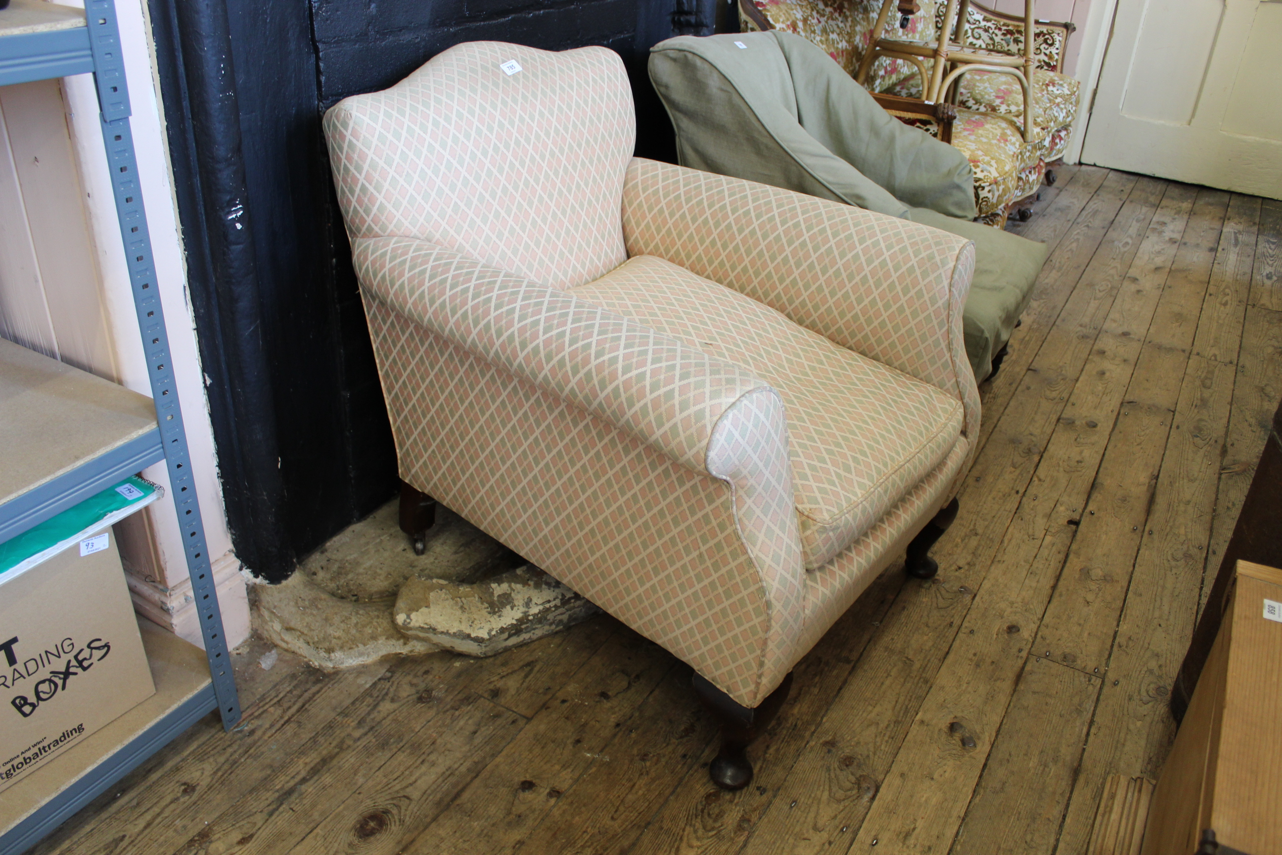 An Edwardian upholstered easy chair on squat cabriole legs