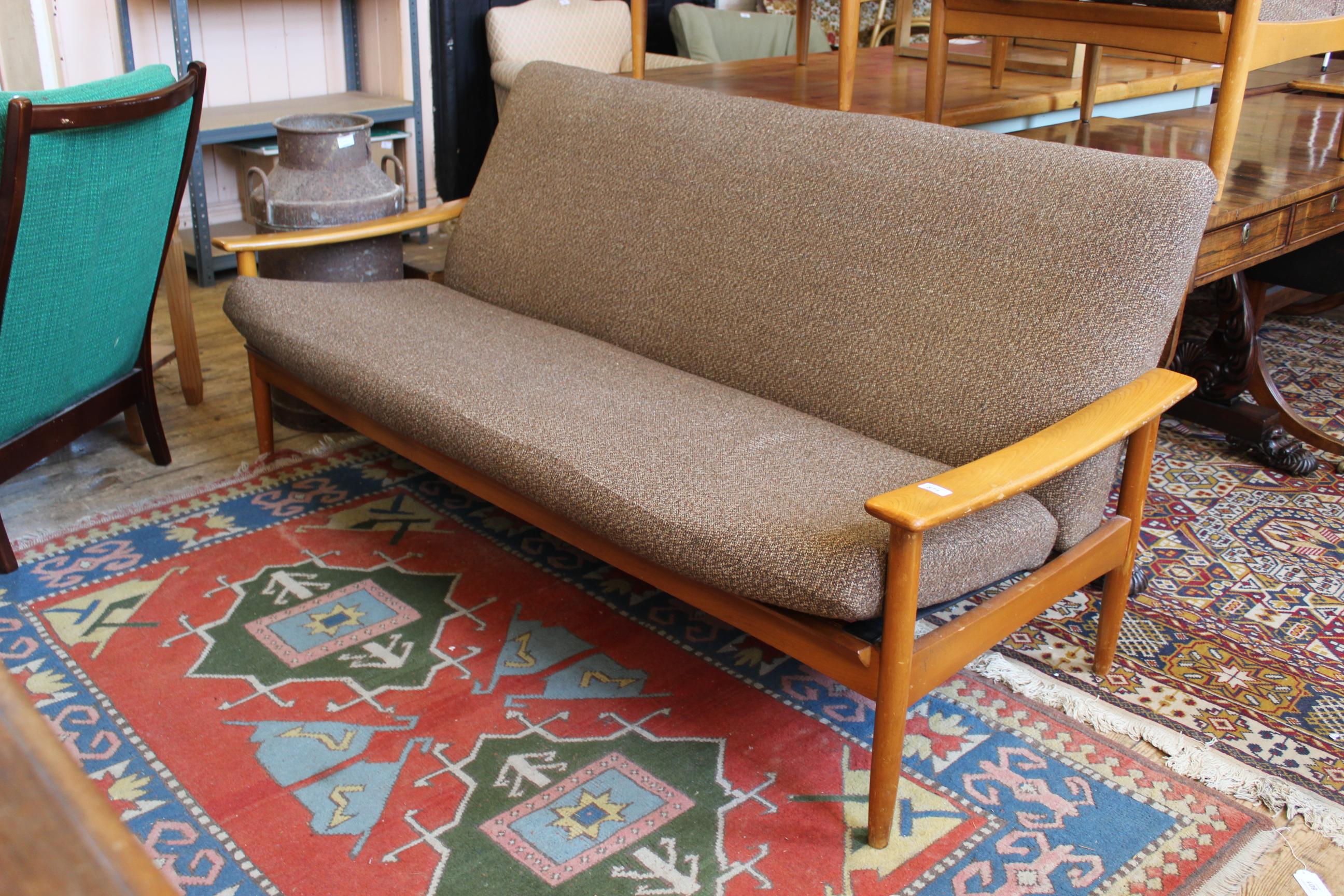 A 1960's Ercol style teak three seater sofa