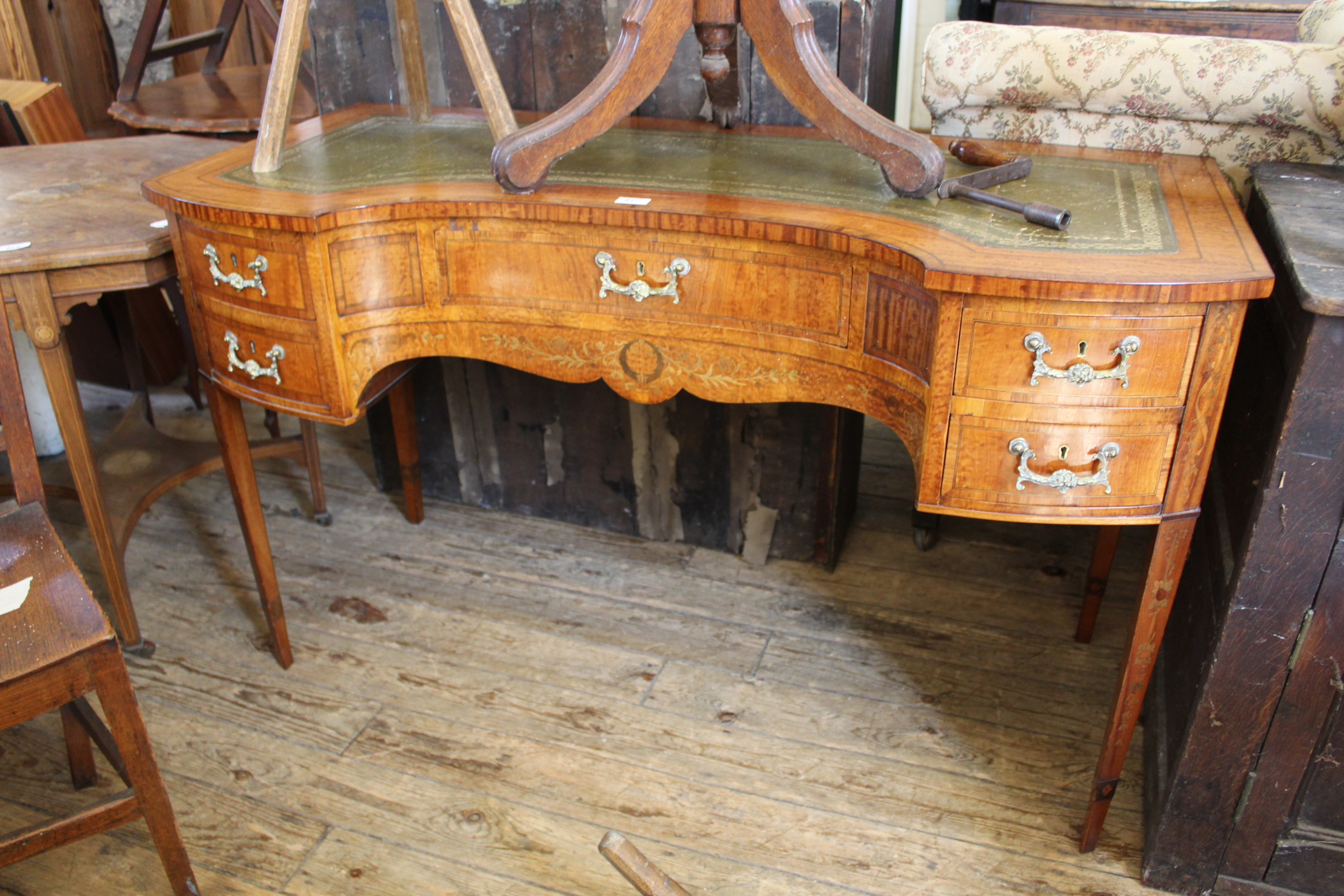 An Edwardian five drawer writing table with concave front,