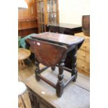 A 17th Century and later oak joint stool/table with carved oval drop leaf top and four baluster