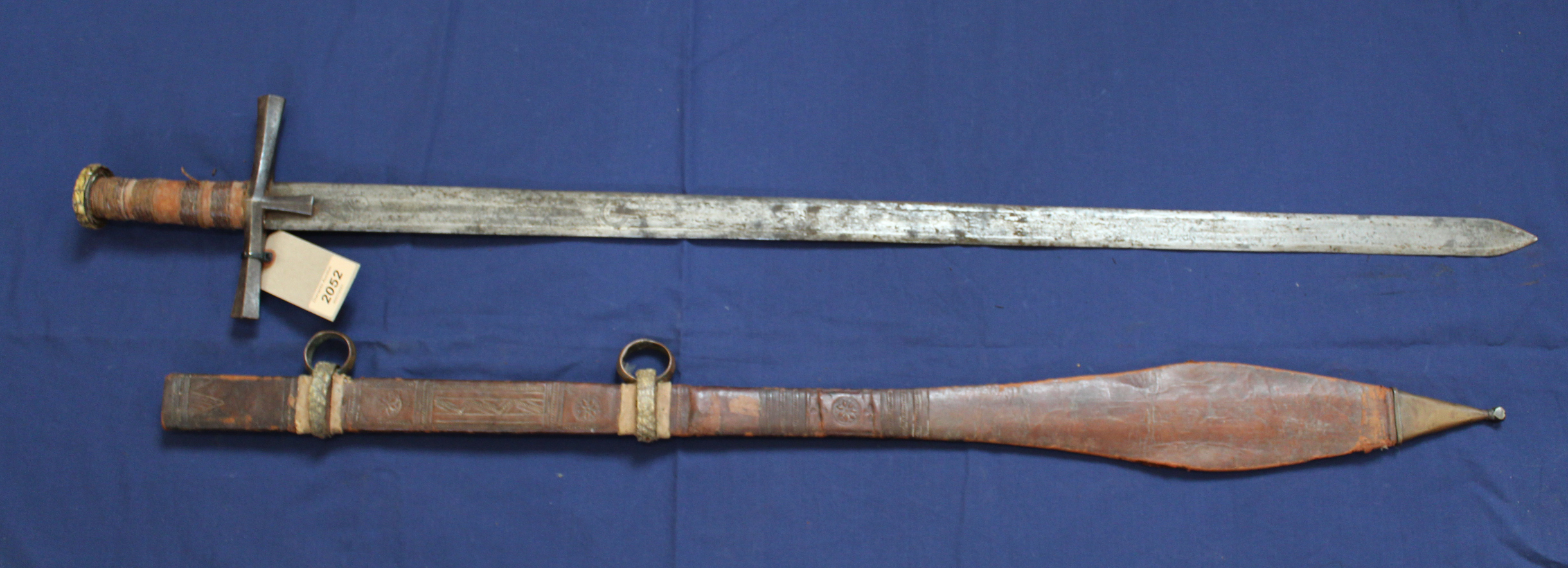 An ethnic sword with leather tooled scabbard