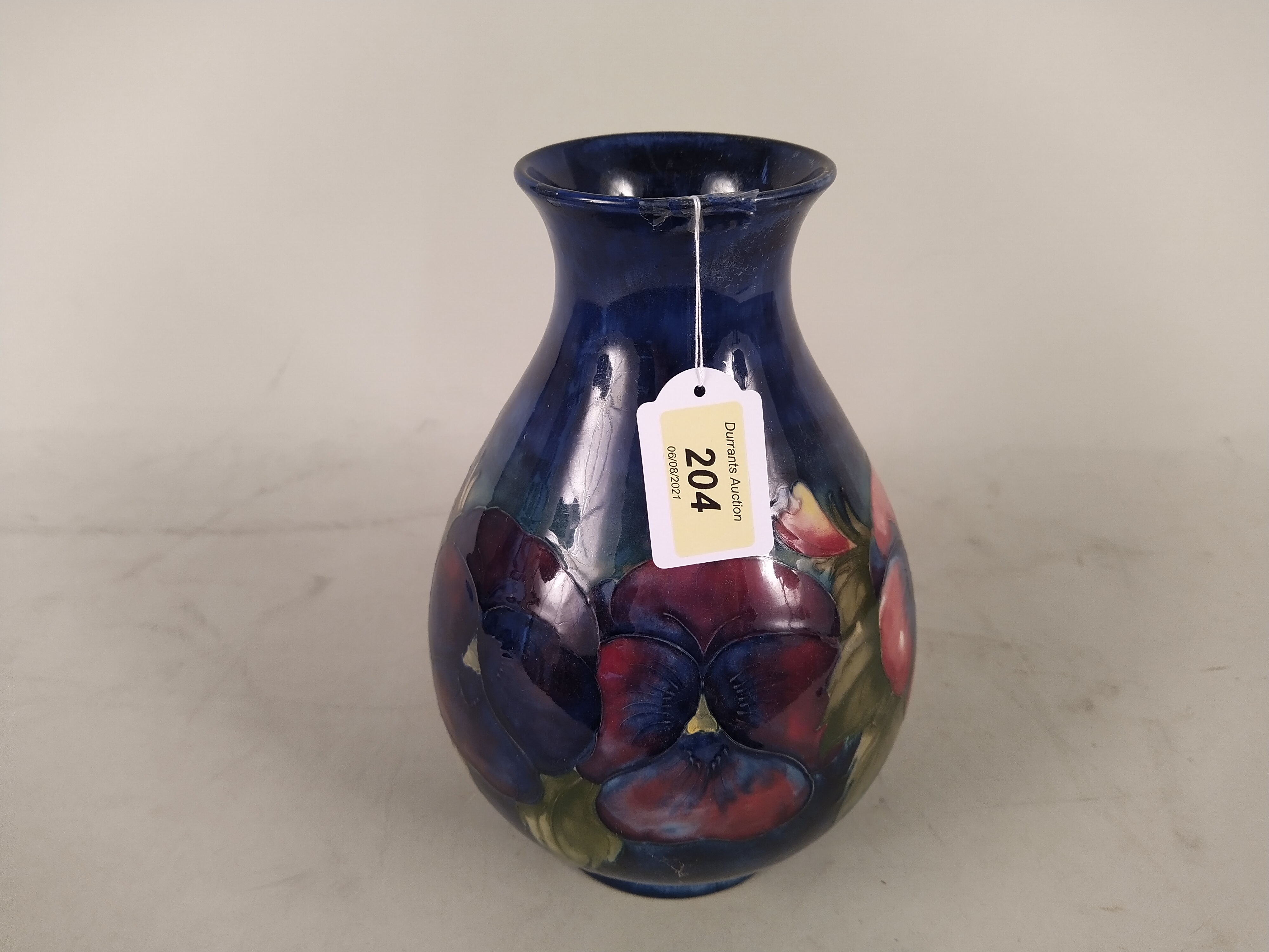 A Moorcroft Pansy pattern vase, bears blue signature and potter to H.M.