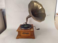 A replica wind-up horn gramophone in an oak case